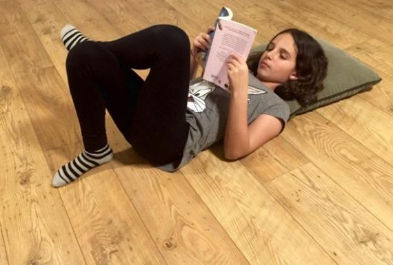 ילדה שוכבת וקורראת ספר על פרקט עץ
