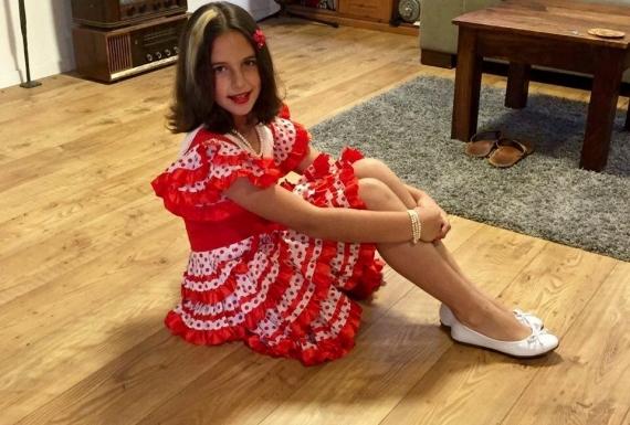 ילדה יושבת על ריצוף פרקט למינציה משכבות עץ לבית