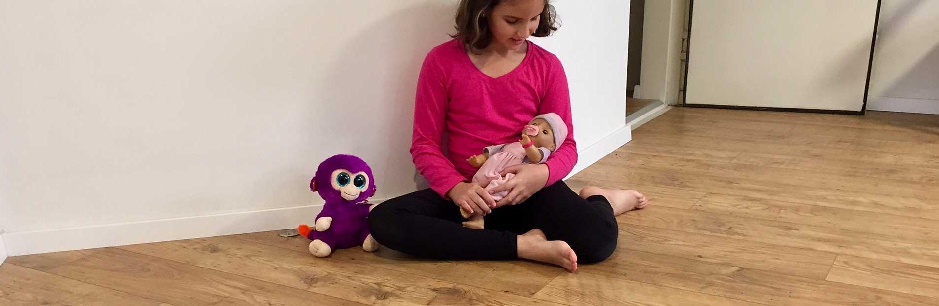 ילדה יושבת על רצפת פרקט