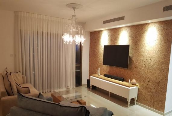 טלוויזיה תלויה על חיפוי קיר שעם הסלון