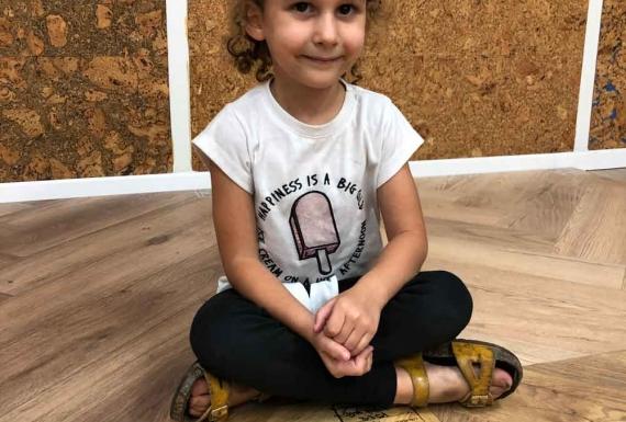 ילדה יושבת על פרקט פישבון למינציה
