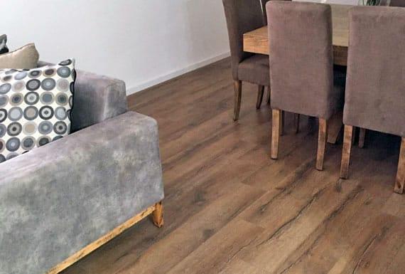 גווני החום והאפור של הסלון ופינת האוכל משתלבים בהרמוניה עם פרקט אלון בגוון מעושן
