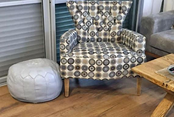 כסא סלון בגווני לבן וחום המשתלב בהרמוניה עם פרקט עץ אלון בדירה ביבנה